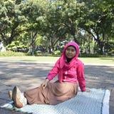 Beautiful female muslim sitting outdoors Royalty Free Stock Image