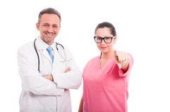 Beautiful female nurse near doctor pointing at you Royalty Free Stock Image