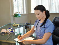 Beautiful female nurse writing stock image
