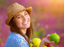 Beautiful female offers an apple. Closeup portrait of happy beautiful female offers an apple, laughing in floral garden, bright sunset light, farming and Stock Images