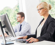 Beautiful female office worker in formalwear with colleague on background Royalty Free Stock Photo