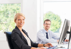 Beautiful female office worker in formalwear with colleague on background Royalty Free Stock Images
