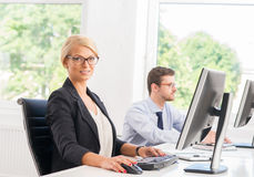 Beautiful female office worker in formalwear with colleague on background Stock Photo