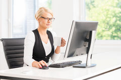 Beautiful female office worker having a break by the computer having a cup of coffee Stock Image