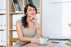 Beautiful female office worker sitting on workplace, smiling, writing down information at her organizer, drinking coffee Stock Images