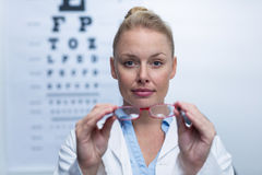 Beautiful female optometrist holding spectacles Royalty Free Stock Image