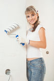 Beautiful female painter near the wall  holding paintroller Royalty Free Stock Image