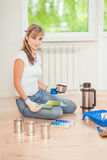 Beautiful female painter sitting on floor and holding color pale Royalty Free Stock Images