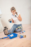 Beautiful female painter sitting on wooden floor and thinking Royalty Free Stock Photography