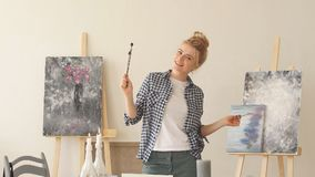 Beautiful female painter wearing stylish casual clothes stretching her arms. As she ia tired of working at her workshop. Happy girl is dancing while painting stock footage