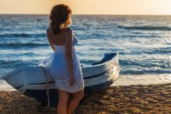 Beautiful female in the pareo near boat on the sand. Beautiful female in white pareo near boat on the sand on sunset Royalty Free Stock Photo