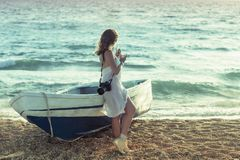 Beautiful female in the pareo near boat on the sand. Beautiful female in white pareo near boat on the sand on sunset Royalty Free Stock Photos