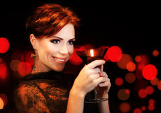 Beautiful female partying, celebrating holiday. Portrait of a woman holding martini glass, girl over black background with red blur bokeh lights, luxury stock photography