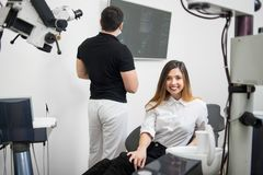 Beautiful female patient sitting in dental chair, smiling after treatment at modern dental clinic. On the background male dentist looking on x-ray picture Stock Photos