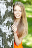 Beautiful female peeping from behind tree Royalty Free Stock Photography