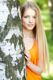 Beautiful female peeping from behind tree Stock Photos