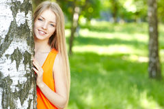 Beautiful female peeping from behind tree Royalty Free Stock Photos