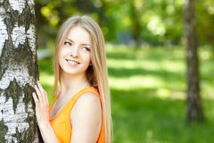 Beautiful female peeping from behind tree Royalty Free Stock Images