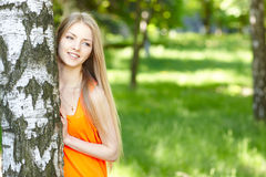 Beautiful female peeping from behind tree Stock Photo