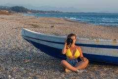 Beautiful female photographer in the bikini with professional camera near boat on the sand. On sunset Royalty Free Stock Photo