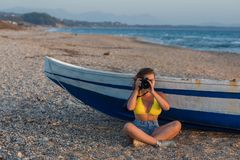 Beautiful female photographer in the bikini with professional camera near boat on the sand. On sunset Stock Photography
