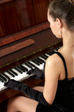 Beautiful female playing piano Stock Photography