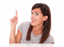 Beautiful female pointing up and smiling at you Royalty Free Stock Image