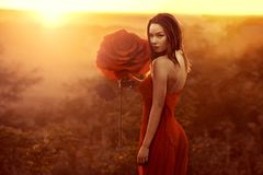 Beautiful female portrait with big paper flowers in the sunset. royalty free stock photo