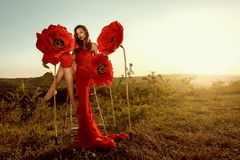 Beautiful female portrait with big paper flowers in the sunset. stock photos