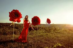 Beautiful female portrait with big paper flowers in the sunset. Stock Photo