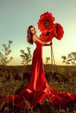 Beautiful female portrait with big paper flowers in the sunset. stock image