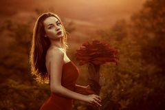 Beautiful female portrait with big paper flowers in the sunset. royalty free stock image