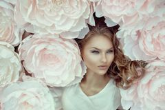 Beautiful female portrait with big white paper flowers. Royalty Free Stock Photography