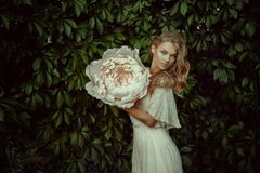 Beautiful female portrait with big white paper flowers. Royalty Free Stock Image