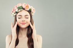 Beautiful female portrait. Healthy spa model wodel with clear skin, brown hair and spring flowers.  stock photo