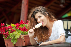 Beautiful female portrait with long brown hair eating ice cream near a pot with red flowers outdoor. Attractive woman Stock Photos