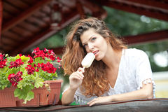 Beautiful female portrait with long brown hair eating ice cream near a pot with red flowers outdoor. Attractive woman Stock Images