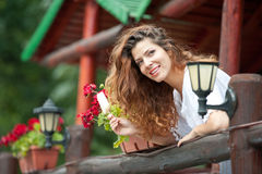 Beautiful female portrait with long brown hair eating ice cream near a pot with red flowers outdoor. Attractive woman Royalty Free Stock Photos
