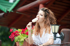 Beautiful female portrait with long brown hair eating ice cream near a pot with red flowers outdoor. Attractive woman Stock Photography