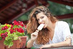 Beautiful female portrait with long brown hair eating ice cream near a pot with red flowers outdoor. Attractive woman Royalty Free Stock Photography