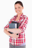 Beautiful female posing with books while standing Stock Images