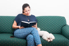 Beautiful female reading a book on sofa. Beautiful female reading a book while her dog is sitting on sofa near her Royalty Free Stock Images