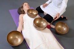 Beautiful female receiving energy sound massage with singing bowls.Isolated on grey background. Royalty Free Stock Photo