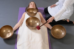 Beautiful female receiving energy sound massage with singing bowls.Isolated on  grey background Royalty Free Stock Images