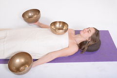 Beautiful female receiving energy sound massage with singing bowls.Isolated on white background Stock Images