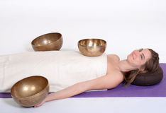 Beautiful female receiving energy sound massage with singing bowls.Isolated on white background Stock Photography