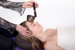 Beautiful female receiving energy sound massage with singing bowls.Isolated on white background Royalty Free Stock Images
