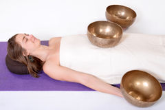 Beautiful female receiving energy sound massage with singing bowls.Isolated on white background Royalty Free Stock Photos