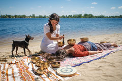 Beautiful female receiving energy sound massage with singing bowls on a river bank stock photos