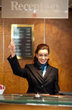 Beautiful female receptionist indicating upwards. To show the direction instructions board Royalty Free Stock Photo